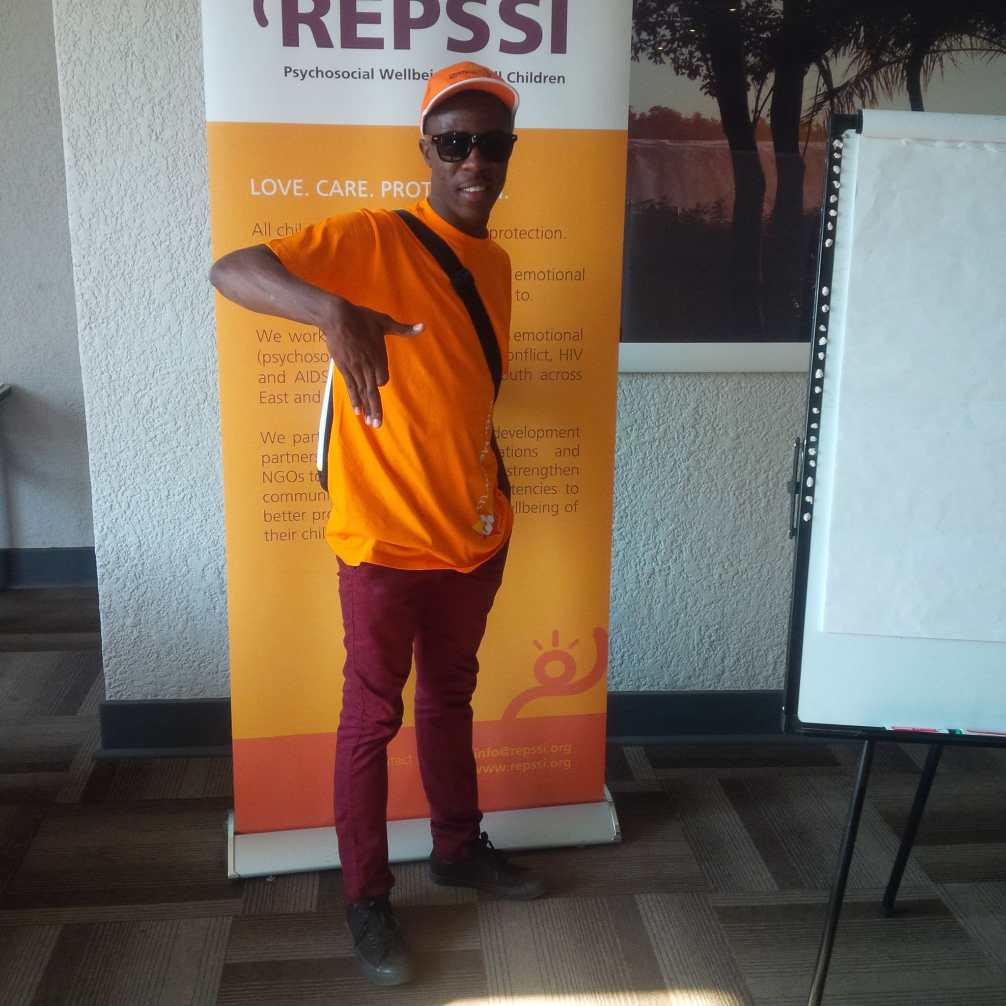Jastes shows his Namibian pride in front of the conference banner, Victoria Falls, Zimbabwe.