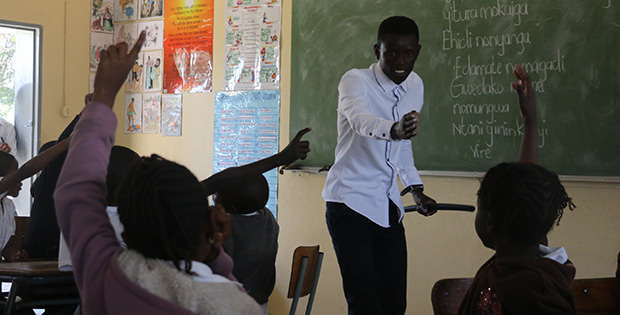 "Petrus Namadiko, 21-year-old graduate of KAYEC's Rundu youth centre, teaches the Grade 2 Rukwangali class at Rundu Junior Primary School, 5 August 2016. He will start his education degree soon - and meanwhile, the teaching strategies that he learned at KAYEC already equip him to lead the class. Every weekday afternoon at KAYEC, two full-time KAYEC youth staff and a team of 15 skilled volunteers offer academic enrichment to the next generation of learners like Namadiko, focusing on math, English and accounting, plus sports, agriculture, culture, leadership training and discussion of relationships that builds on what learners get in school. Today, other teachers have already adopted Namadiko's language-learning methods. Says Principal Kerttau Aisindi: ""He's good! He knows how to communicate with learners."""